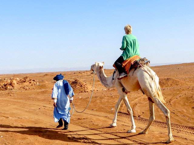 Char Selsvold riding camel in Morocco.